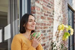 Woman relaxing outside with cup of coffee